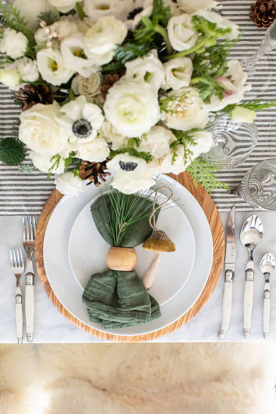Christmas table setting, green napkin, olive wood charger, white plates from Williams Sonoma.