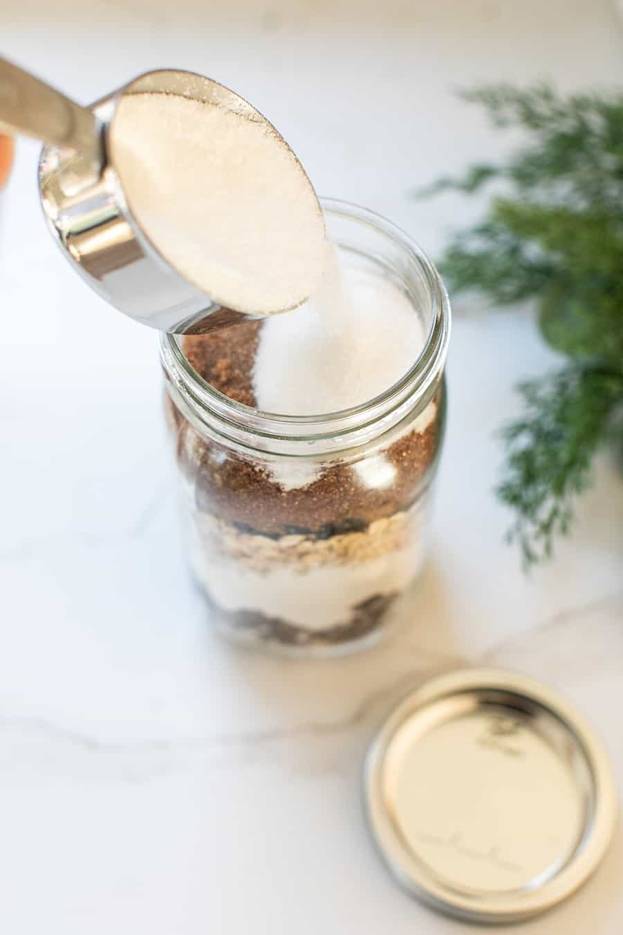 Pouring sugar to cookie mix in a jar