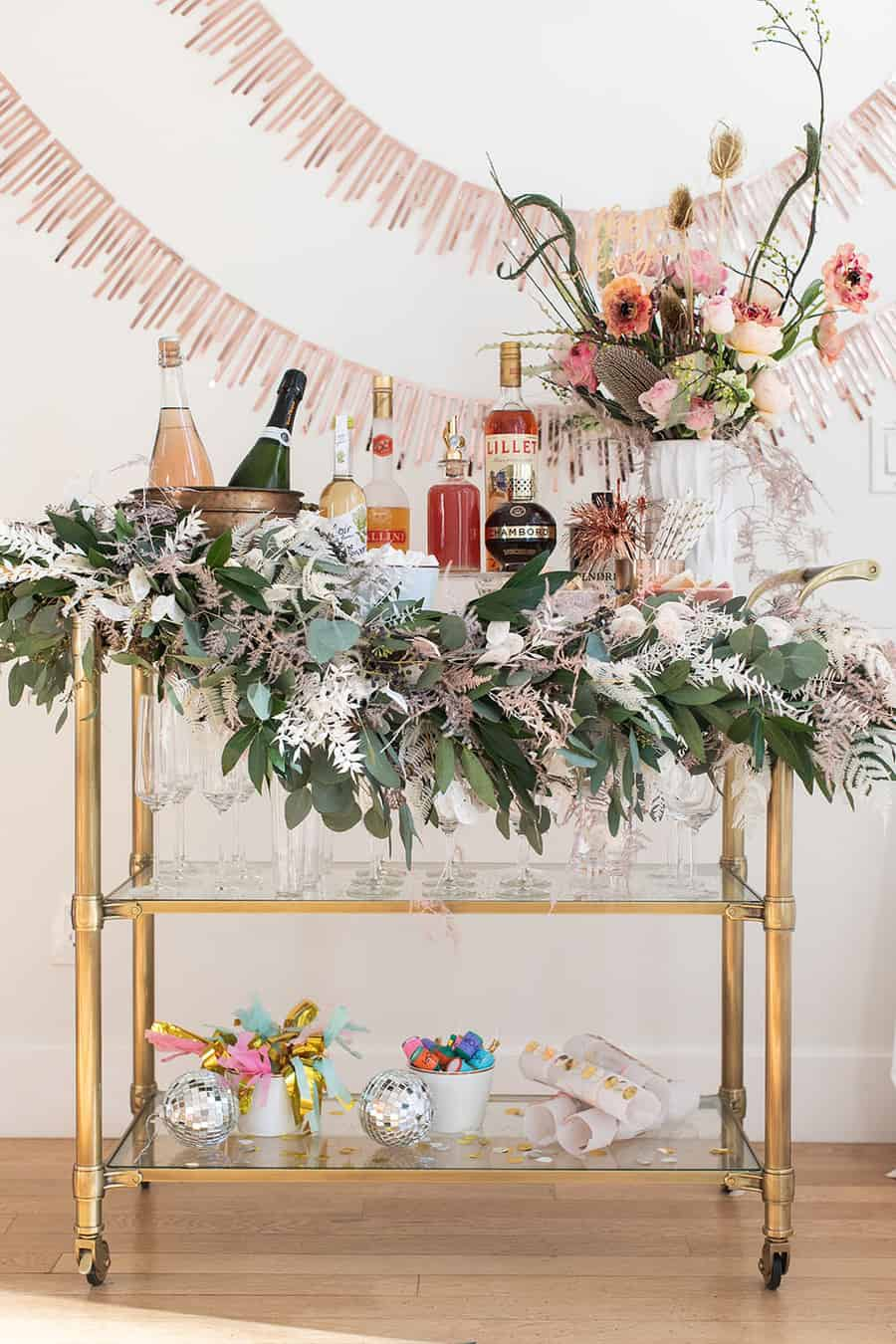 New Year's Eve Champagne Bar with garland, glasses, flowers and decorations.