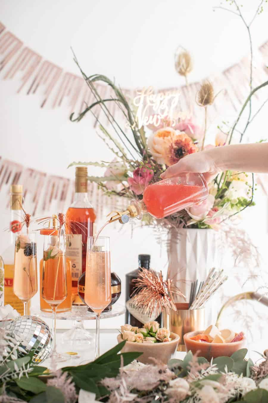 Pouring in juice to a glass of Champagne for a New Year's Eve Champagne Bar