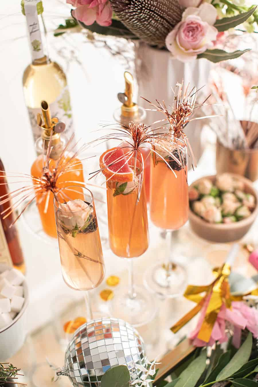Festive Champagne cocktails for New Year's Eve with flowers, sparklers and berries.