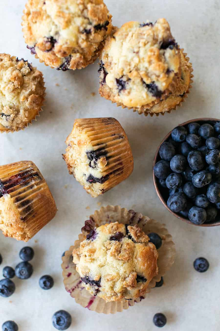 Blueberry muffins on a marble table with fresh blueberries