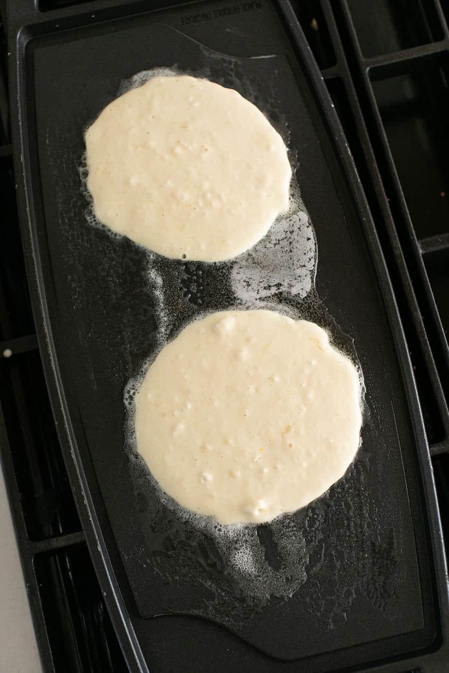 Two dollops of pancake batter on a hot griddle