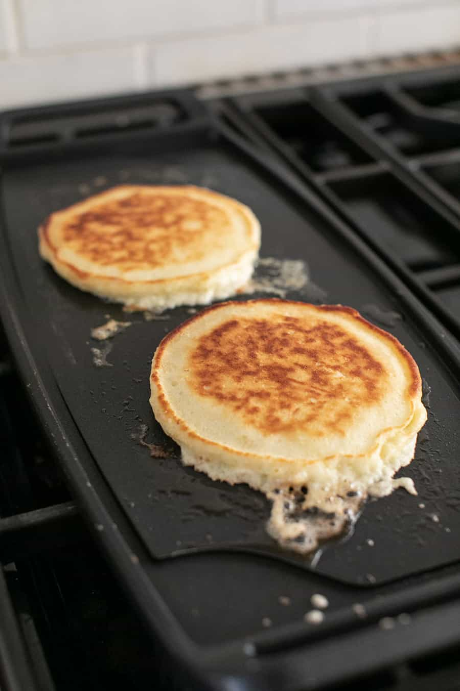 Fluffy pancakes cooking on a griddle.