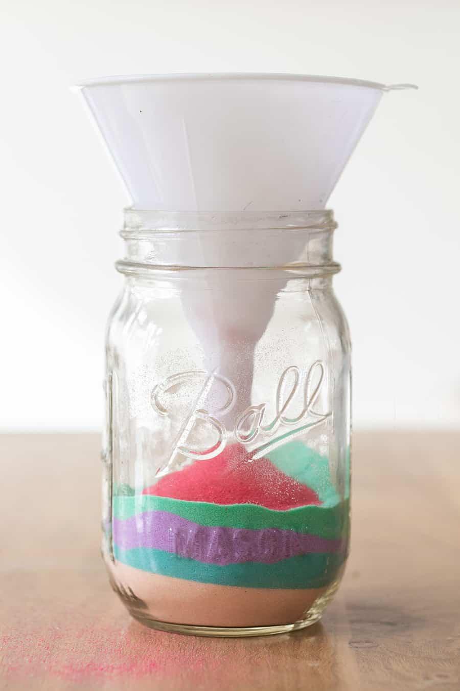 Funneling sand art into a ball mason jar