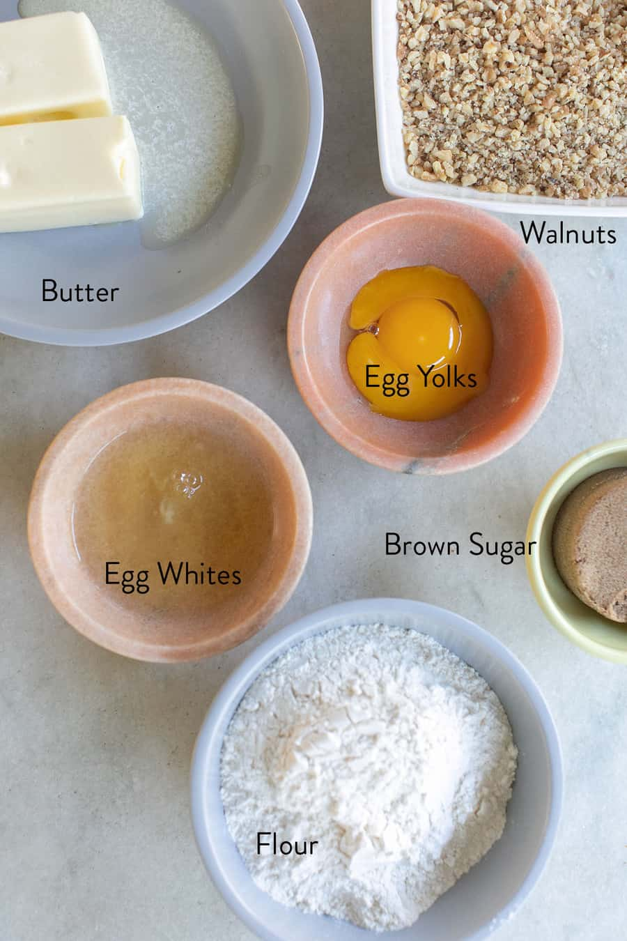Butter, egg yolks, egg whites, flour, crushed walnuts and brown sugar in bowls on a marble table to make cookies.