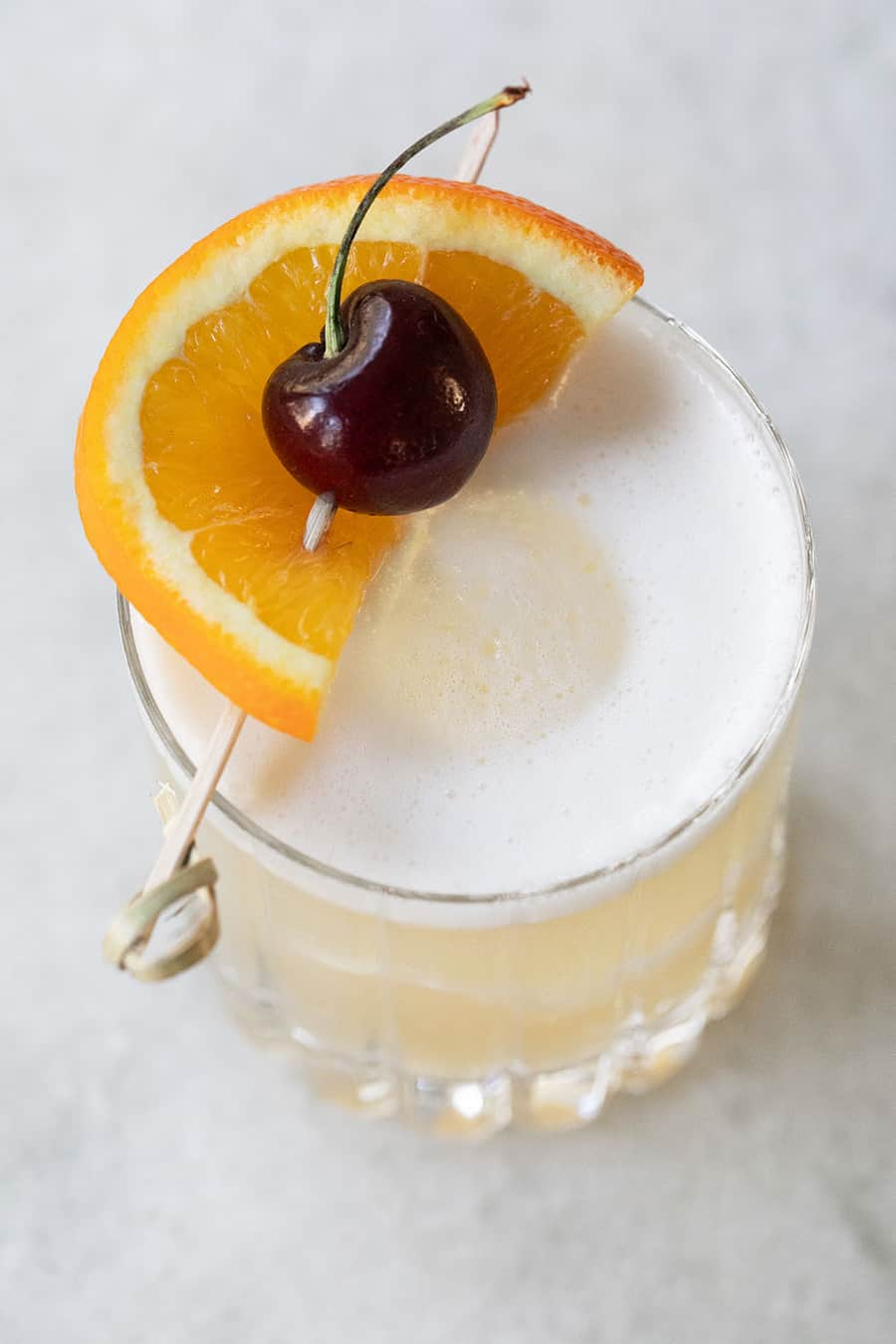 Whiskey sour with an orange slice and fresh cherry on top.