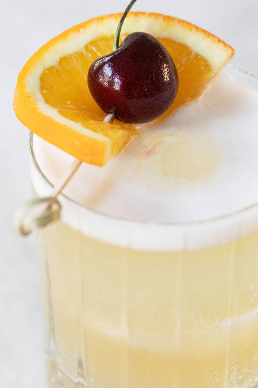 Cherry and orange slice garnish on a whiskey sour