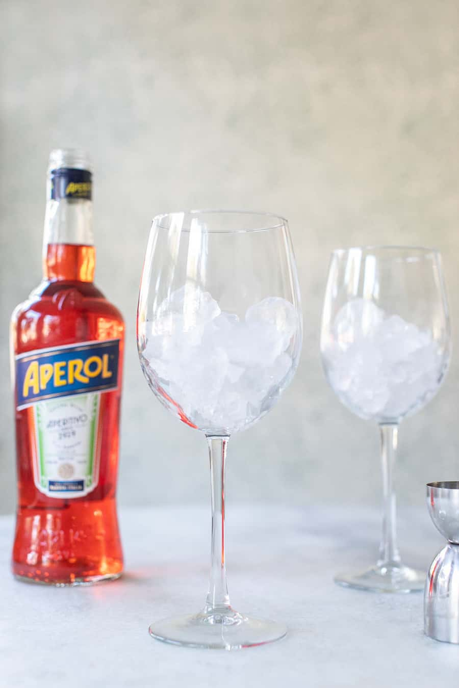 Wine glass filled with ice and a bottle of Aperol