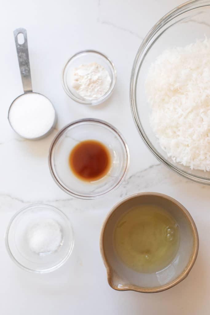coconut, egg whites, vanilla, salt and sugar in bowls