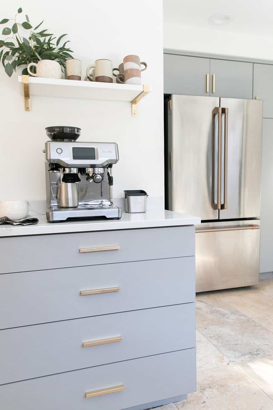 Gray kitchen cabins, gold pulls, cafe appliances and espresso maker