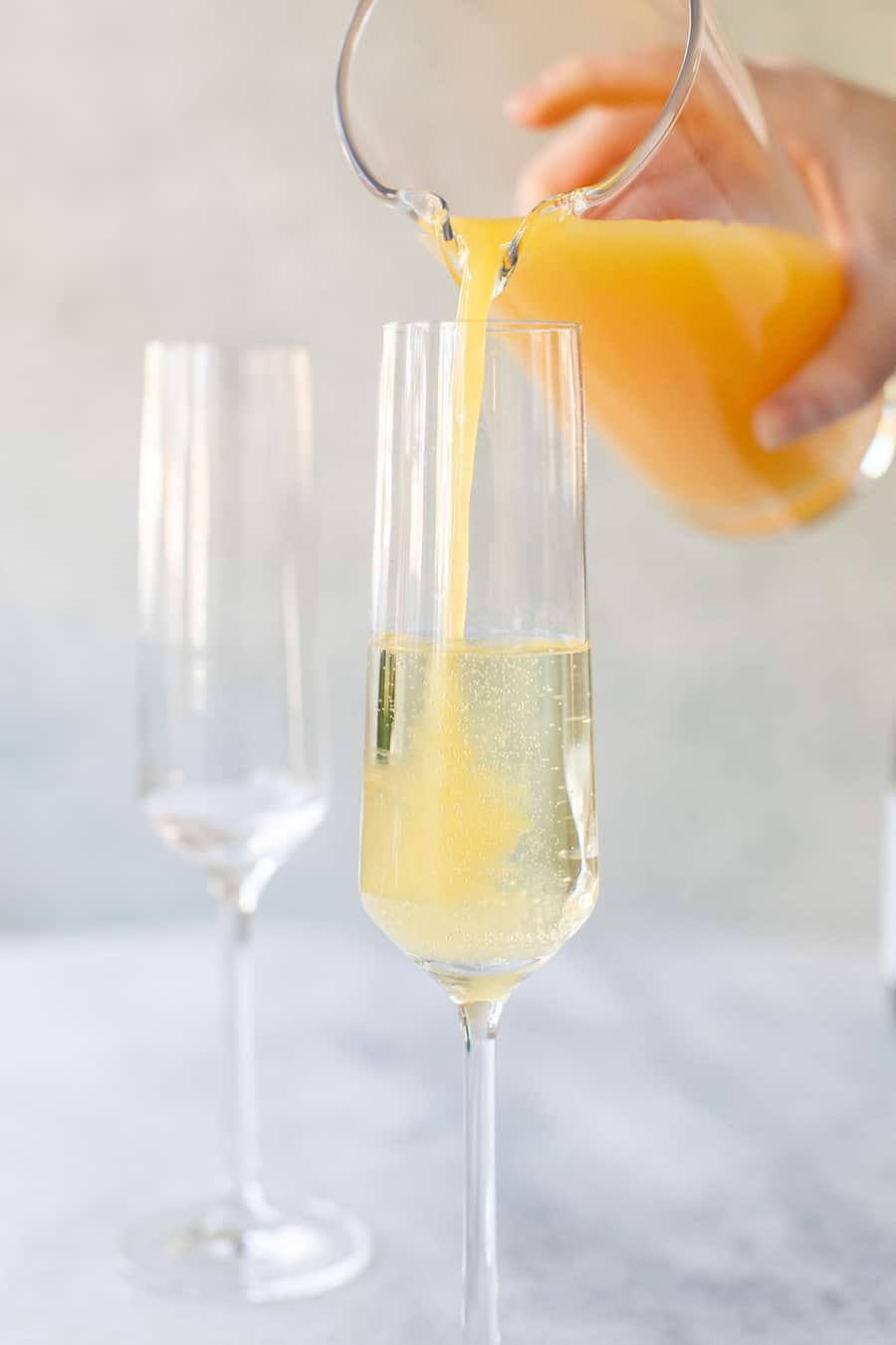 Pouring orange juice into sparkling wine in a Champagne flute