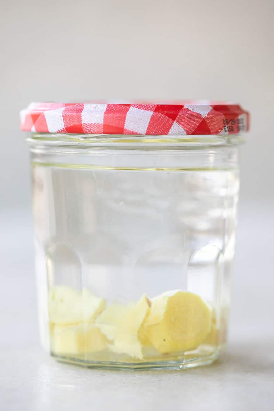 Homemade Ginger vodka with chunks of ginger on a jar