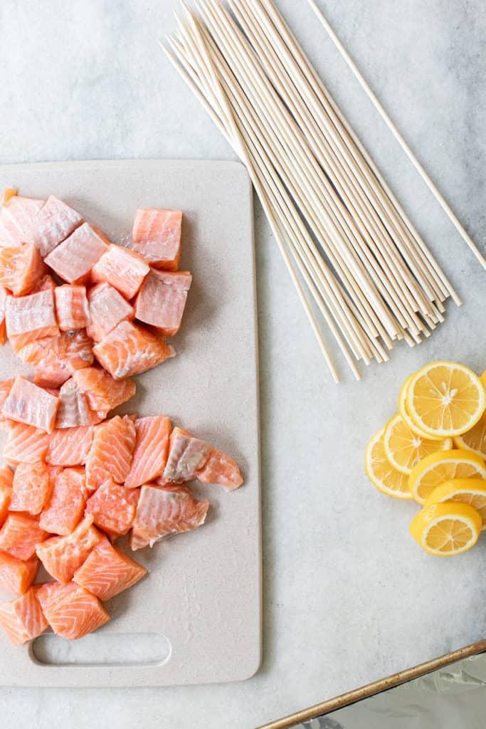 raw salmon cut, lemon slices, wooden skewers