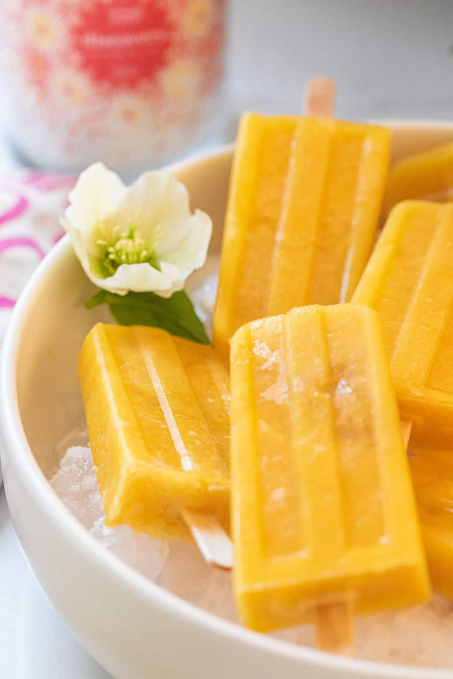 Mango popsicles on ice with flower