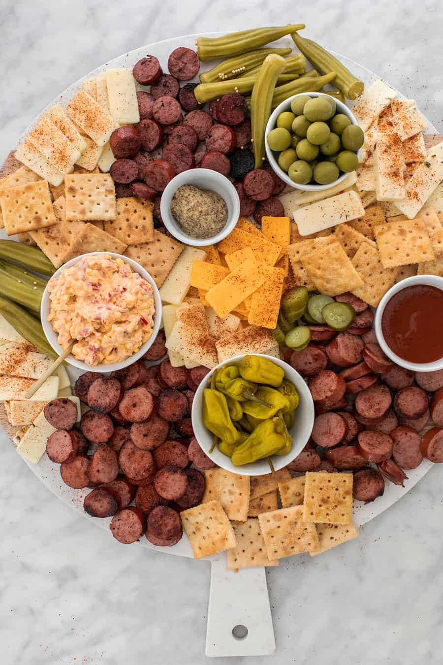 Cheese and meat platter with crackers, sausage, cheese, pimento cheese, pickles and olives.