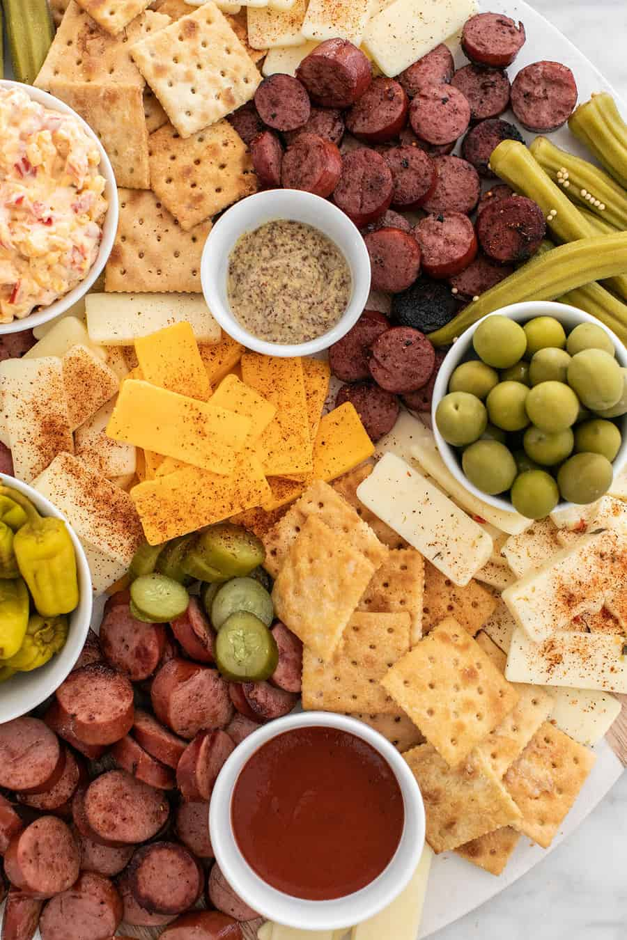 Souther charcuterie board with sausage, cheese, pickled vegetables, olives, pimento cheese and crackers.