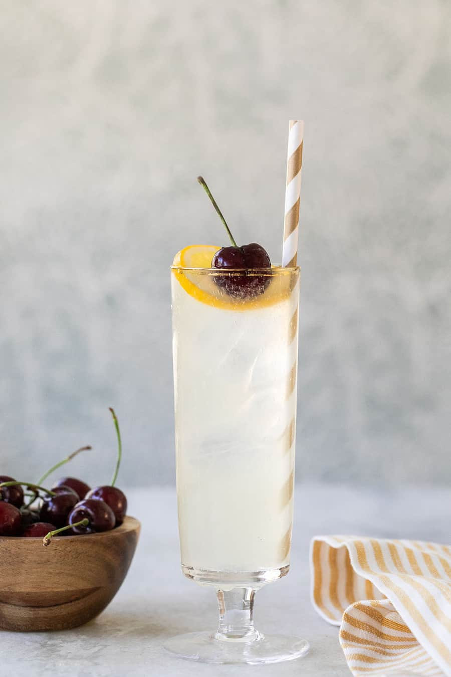 cocktail with lemon, simple syrup, gin and afresh cherry