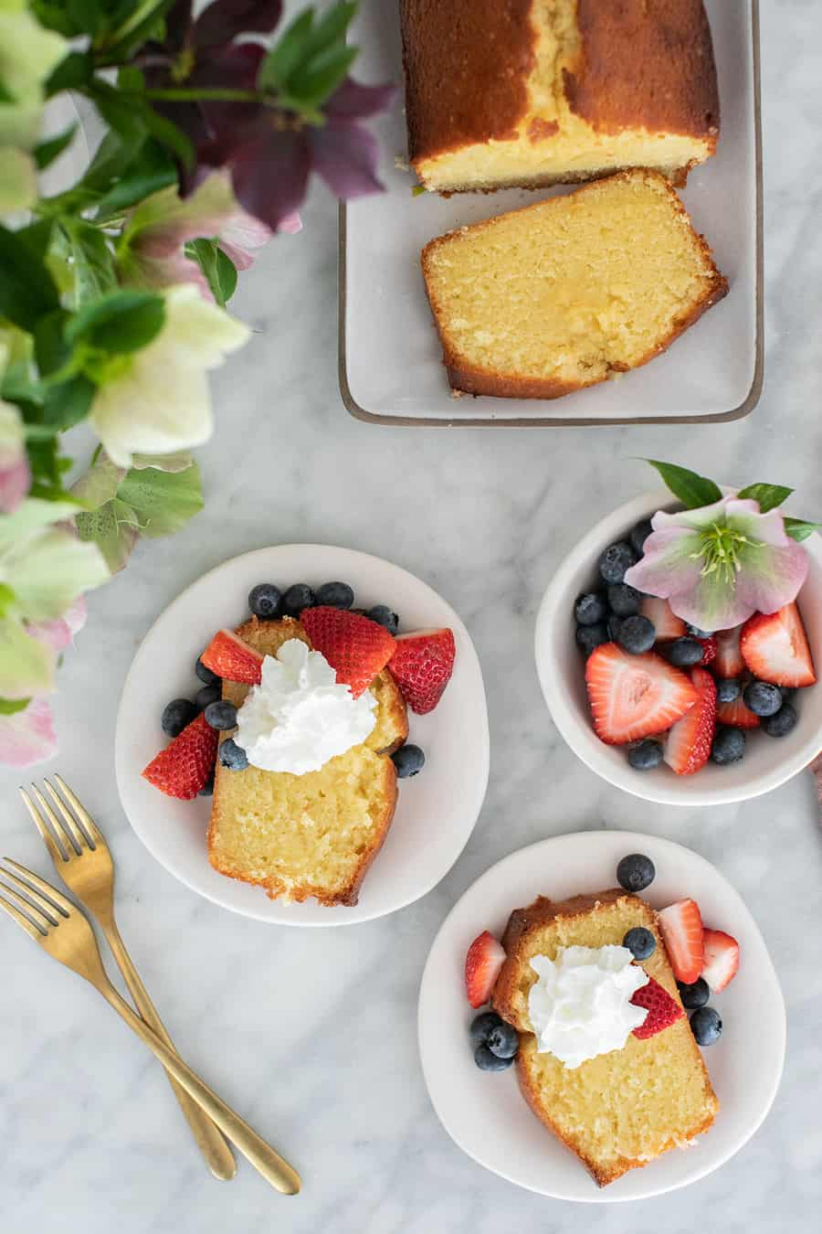 Pound cake on plate sliced with whipped cream and strawberries