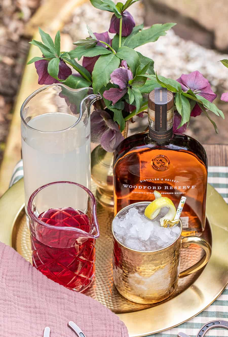 Cranberry juice, lemonade, Woodford Reserve on a gold tray.