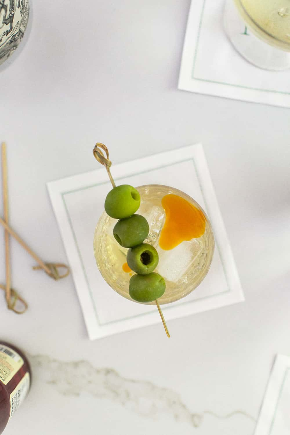Dirty martini with 4 green olives and a dash of chili oil over the top.