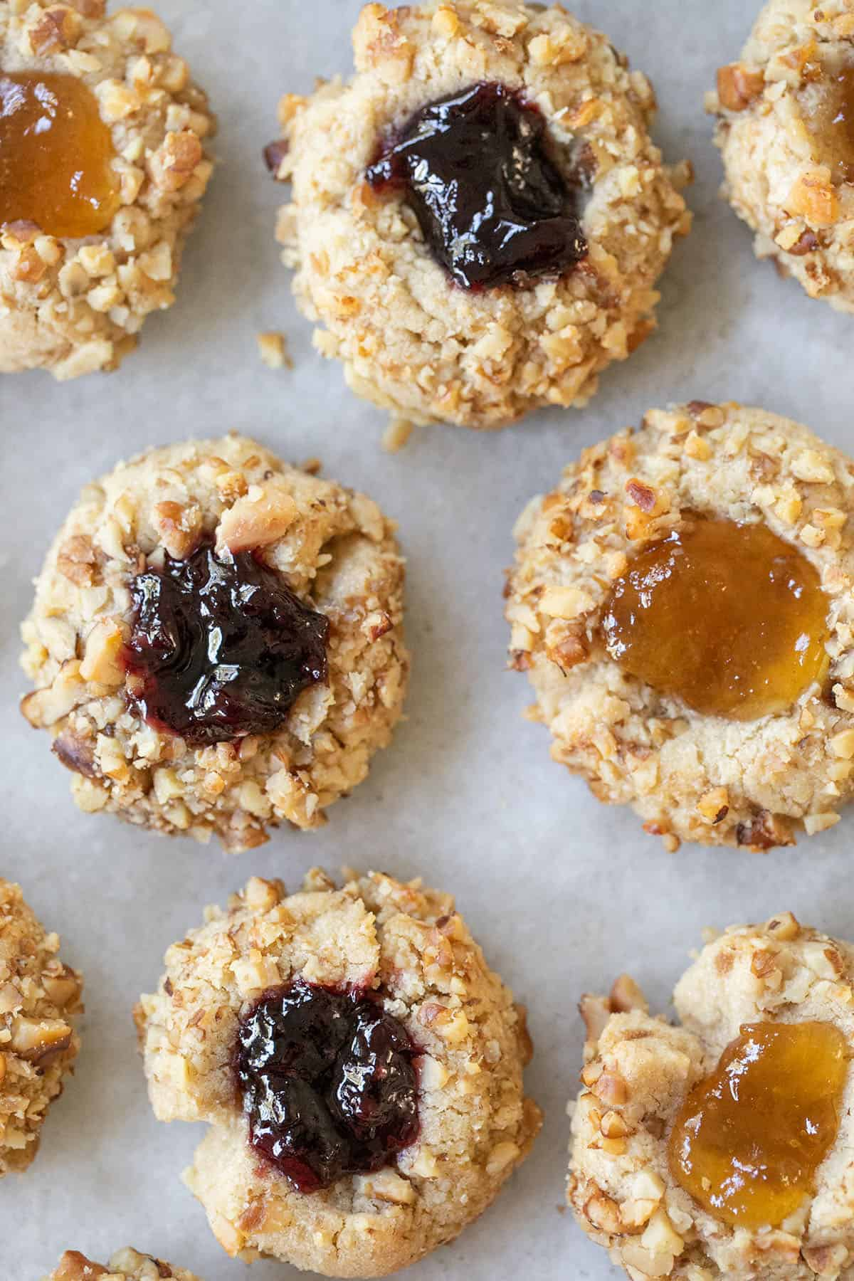 Thumbprint cookies with rolled walnuts and filled with jam.