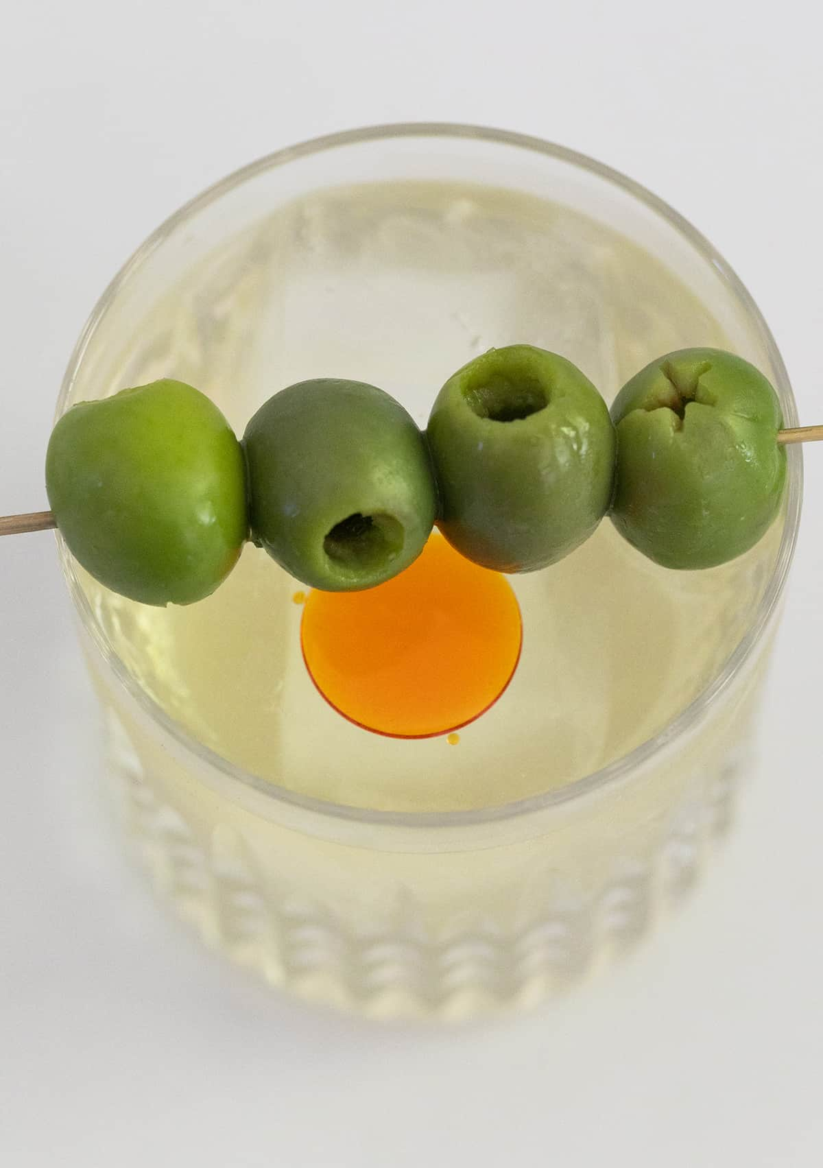 Green olives sitting over a dirty martini
