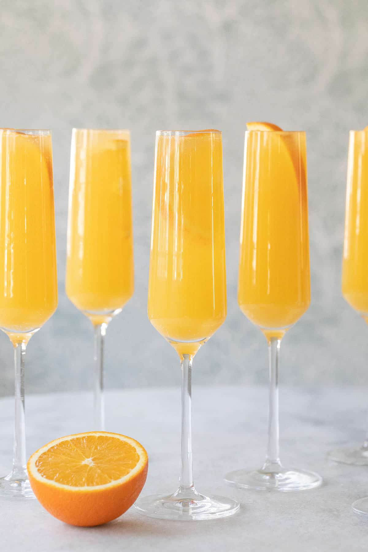 Mimosas on a table are cheap alcoholic drinks to make