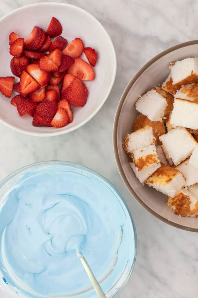 sliced strawberries and blue whipped cream