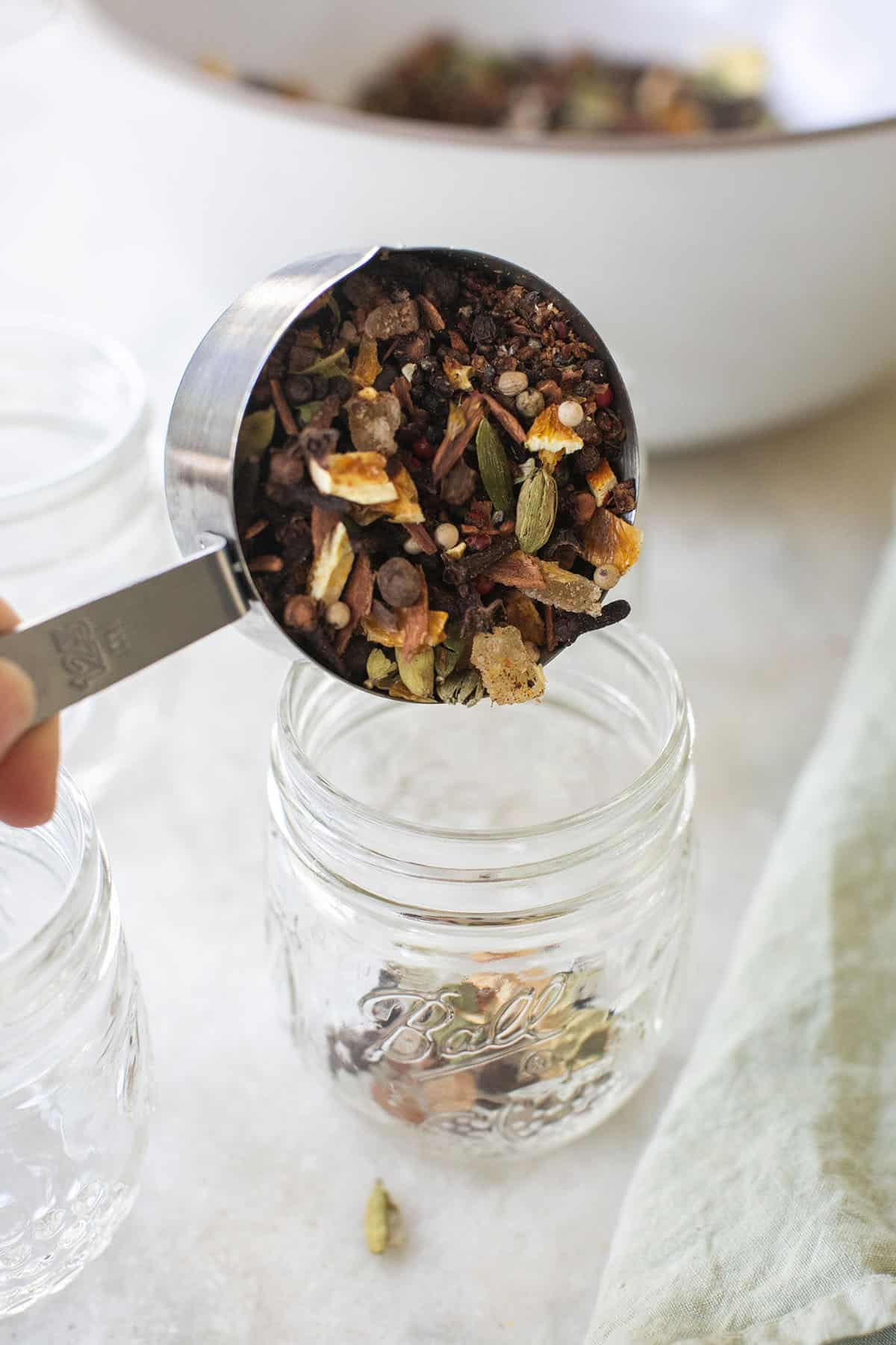 scooping mulled wine spices into a jar