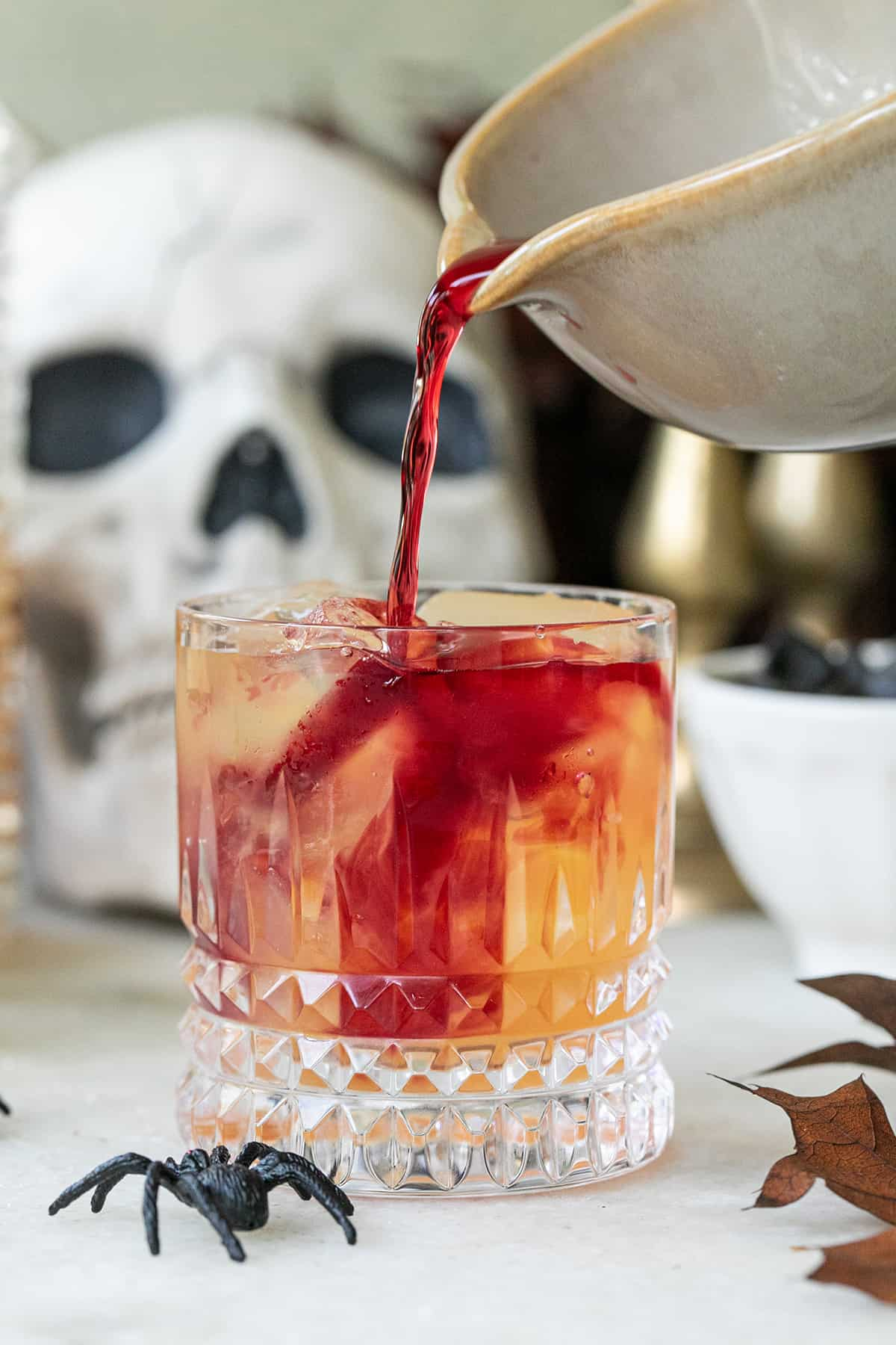 pouring pomegranate juice over a halloween cocktail